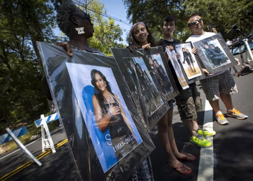 Fans hold pictures of Bobbi Kristina Brown and Whitney Houston as they stand outside the Fairview Cemetery in Westfield, New Jersey, where Bobbi Kristina's burial service is taking place, August 3, 2015. REUTERS/MIKE SEGAR