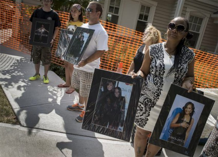 Fans hold pictures of Bobbi Kristina Brown and Whitney Houston as they stand outside the Fairview Cemetery in Westfield, New Jersey, where Bobbi Kristina's burial service is held, August 3, 2015. REUTERS/MIKE SEGAR