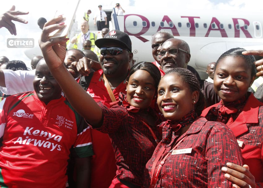 Kenya Airways cabin crew take selfies with Sevens Rugby team coach Benjamin Ayimba (in cap) and airline CEO Mbuvi Nguze (in glasses right) upon landing at the JKIA on April 19, 2016. Kenya 7s team beat Fiji 30-7 in the final of the Singapore Sevens to capture their first World Series event. Photo/Stafford Ondego/www.sportpicha.com