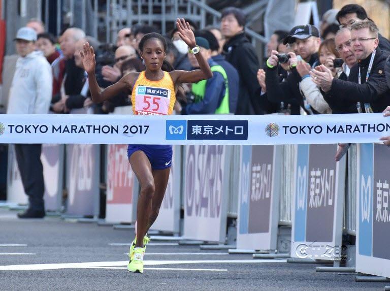Kenya's Sarah Chepchirchir (C, #55) crosses the finish line in the women's category of the Tokyo Marathon in Tokyo on February 26, 2017. PHOTO/KAZUHIRO NOGI / AFP