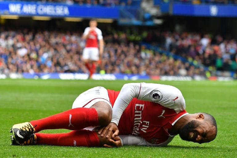 Arsenal's French striker Alexandre Lacazette lies injured after a collision with Chelsea's Nigerian midfielder Victor Moses (not pictured) during the English Premier League football match between Chelsea and Arsenal at Stamford Bridge in London.Image/AFP
