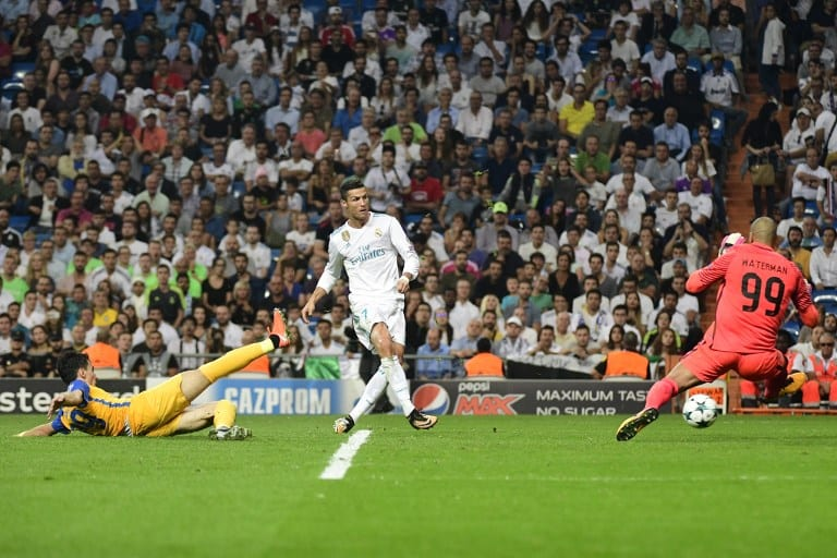 Real Madrid's forward from Portugal Cristiano Ronaldo (C) kicks the ball past APOEL Nicosia's goalkeeper from the Netherlands Boy Waterman during the UEFA Champions League football match Real Madrid CF vs APOEL FC at the Santiago Bernabeu stadium in Madrid on September 13.