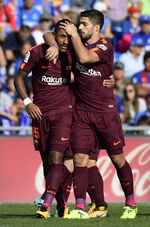 Barcelona's forward from Uruguay Luis Suarez (R) congratulates Barcelona's midfielder from Brazil Paulinho after scoring a goal during the Spanish league football match Getafe CF vs FC Barcelona at the Col. Alfonso Perez stadium in Getafe .AFP PHOTO /