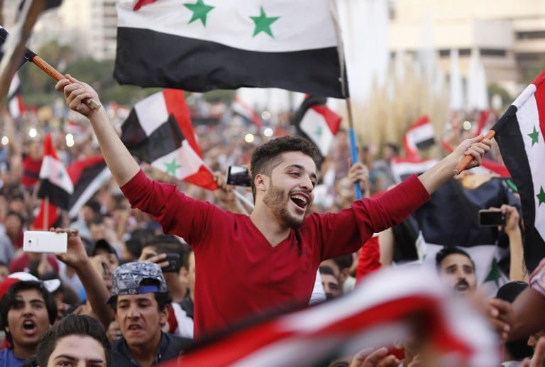Syrians wave their national flag as they celebrate in Damascus' Umayyad Square on October 5, 2017, after Syria's national football team scored in the first leg of the FIFA World Cup 2018 qualifier between Syria and Australia. Syria drew with Australia 1-1. / AFP PHOTO .