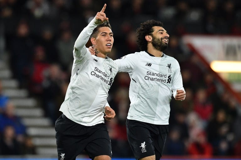 Liverpool's Brazilian midfielder Roberto Firmino (L) celebrates with Liverpool's Egyptian midfielder Mohamed Salah after scoring their fourth goal during the English Premier League football match between Bournemouth and Liverpool at the Vitality Stadium in Bournemouth, southern England on December 17, 2017. / AFP PHOTO / Glyn KIRK