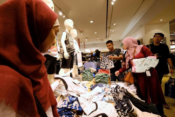 Costumers holds a cloths during late night Ramadan shopping at Gandaria Mall in Jakarta, Indonesia, June 10, 2017. Picture take June 10, 2017. REUTERS/Beawiharta